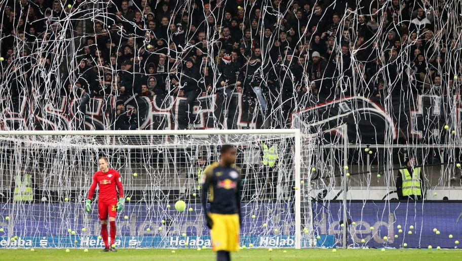 Fans throw tennis balls on the pitch to protest against football games scheduled on Mondays (Montagsspiele) during the German First division Bundesliga football match Eintracht Frankfurt vs RB Leipzig in Frankfurt, Germany, on February 19, 2018. / AFP PHOTO / Daniel ROLAND / RESTRICTIONS: DURING MATCH TIME: DFL RULES TO LIMIT THE ONLINE USAGE TO 15 PICTURES PER MATCH AND FORBID IMAGE SEQUENCES TO SIMULATE VIDEO. == RESTRICTED TO EDITORIAL USE == FOR FURTHER QUERIES PLEASE CONTACT DFL DIRECTLY AT + 49 69 650050  / RESTRICTIONS: DURING MATCH TIME: DFL RULES TO LIMIT THE ONLINE USAGE TO 15 PICTURES PER MATCH AND FORBID IMAGE SEQUENCES TO SIMULATE VIDEO. == RESTRICTED TO EDITORIAL USE == FOR FURTHER QUERIES PLEASE CONTACT DFL DIRECTLY AT + 49 69 650050        (Photo credit should read DANIEL ROLAND/AFP/Getty Images)