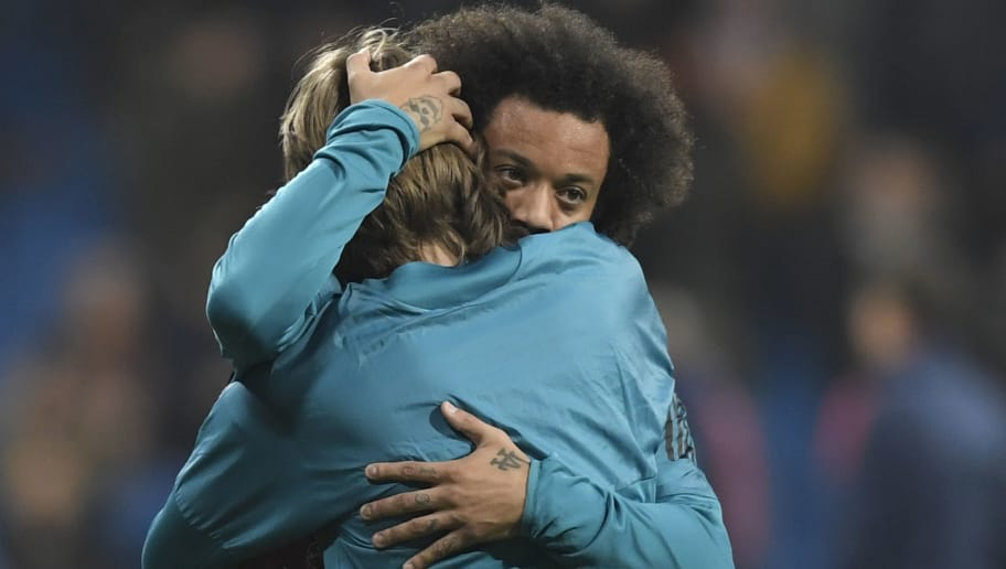 Real Madrid's Brazilian defender Marcelo (R) hugs Real Madrid's Croatian midfielder Luka Modric before the UEFA Champions League round of sixteen first leg football match Real Madrid CF against Paris Saint-Germain (PSG) at the Santiago Bernabeu stadium in Madrid on February 14, 2018.   / AFP PHOTO / GABRIEL BOUYS        (Photo credit should read GABRIEL BOUYS/AFP/Getty Images)