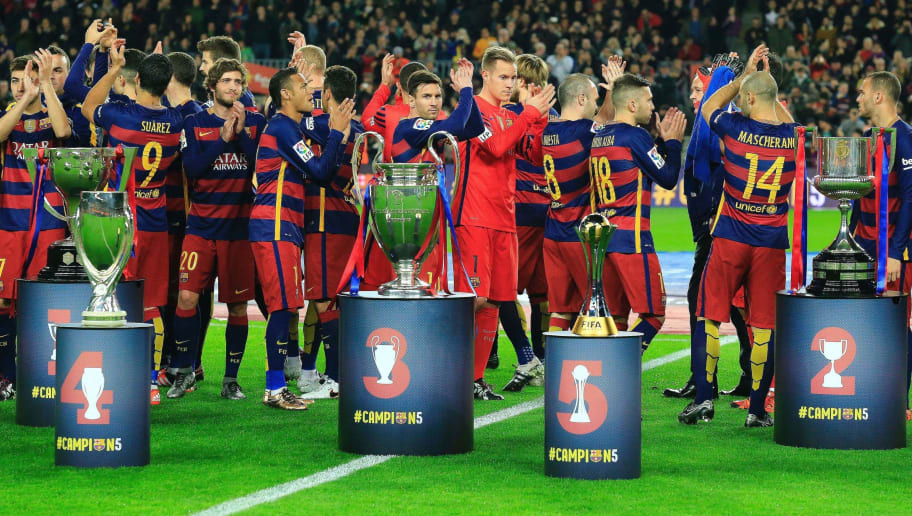 FC Barcelona players applaud after posing with their five trophies (FromL) Spanish Liga, UEFA Super Cup, UEFA Champions League, FIFA Club World Cup and Spanish Copa del Rey (King's Cup) before the Spanish league football match FC Barcelona vs Real Betis Balompie at the Camp Nou stadium in Barcelona on December 30, 2015. AFP PHOTO/ PAU BARRENA / AFP / PAU BARRENA        (Photo credit should read PAU BARRENA/AFP/Getty Images)
