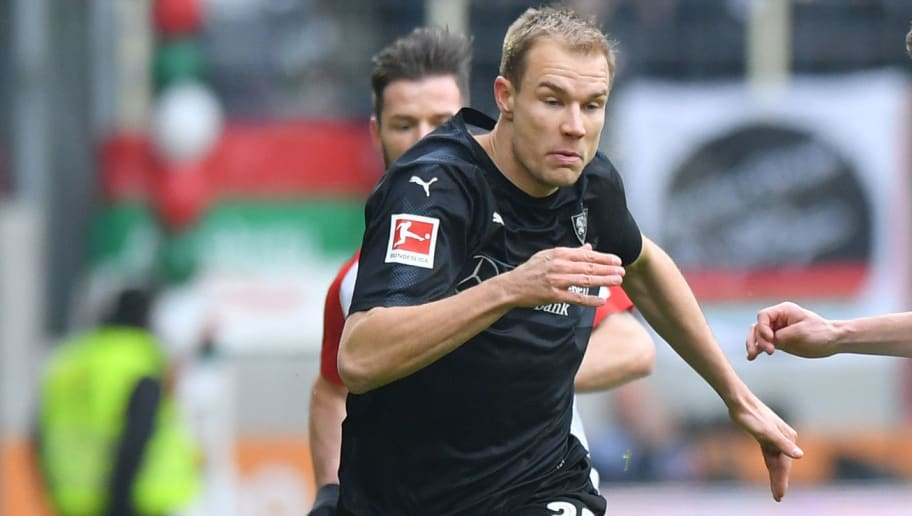 AUGSBURG, GERMANY - FEBRUARY 18: Holger Badstuber of Stuttgart and Raphael Framberger of Augsburg compete for the ball during the Bundesliga match between FC Augsburg and VfB Stuttgart at WWK-Arena on February 18, 2018 in Augsburg, Germany. (Photo by Sebastian Widmann/Bongarts/Getty Images)