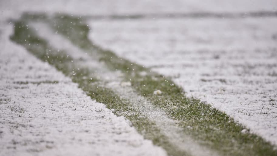 HANOVER, GERMANY - DECEMBER 10: Line is cleared on the pitch during heavy snow storm during the Bundesliga match between Hannover 96 and TSG 1899 Hoffenheim at HDI-Arena on December 10, 2017 in Hanover, Germany. (Photo by Stuart Franklin/Bongarts/Getty Images)