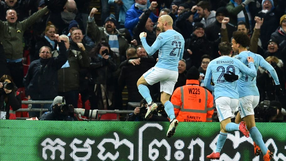 Manchester City's Spanish midfielder David Silva (L) celebrates after scoring their third goal during the English League Cup final football match between Manchester City and Arsenal at Wembley stadium in north London on February 25, 2018. / AFP PHOTO / Glyn KIRK / RESTRICTED TO EDITORIAL USE. No use with unauthorized audio, video, data, fixture lists, club/league logos or 'live' services. Online in-match use limited to 75 images, no video emulation. No use in betting, games or single club/league/player publications.  /         (Photo credit should read GLYN KIRK/AFP/Getty Images)