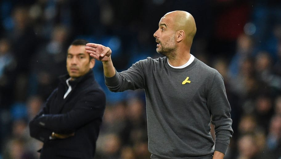Manchester City's Spanish manager Pep Guardiola watches from the touchline wearing a yellow ribbon, a symbol used by Catalan separatists in Spain, during the UEFA Champions League Group F football match between Manchester City and Feyenoord at the Etihad Stadium in Manchester, north west England, on November 21, 2017. / AFP PHOTO / Oli SCARFF        (Photo credit should read OLI SCARFF/AFP/Getty Images)
