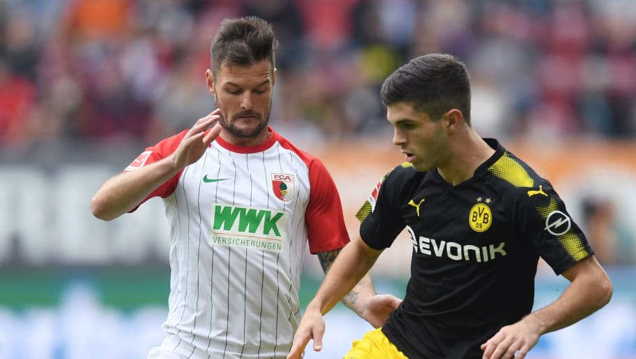Augsburg's German midfielder Marcel Heller (L) and Dortmund's US midfielder Christian Pulisic (R) vie for the ball during the German first division Bundesliga football match between FC Augsburg and Borussia Dortmund in Augsburg, southern Germany on September 30, 2017. / AFP PHOTO / Christof STACHE / RESTRICTIONS: DURING MATCH TIME: DFL RULES TO LIMIT THE ONLINE USAGE TO 15 PICTURES PER MATCH AND FORBID IMAGE SEQUENCES TO SIMULATE VIDEO. == RESTRICTED TO EDITORIAL USE == FOR FURTHER QUERIES PLEASE CONTACT DFL DIRECTLY AT + 49 69 650050         (Photo credit should read CHRISTOF STACHE/AFP/Getty Images)
