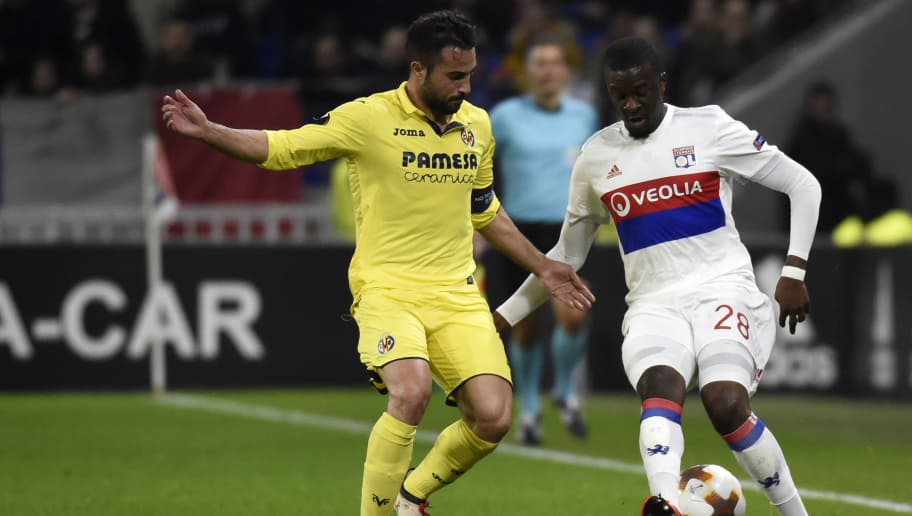 Villarreal's Spanish defender Mario Gaspar (L) fights for the ball with Lyon's French defender Tanguy Ndombele (R) during the Europa League (C3) football match Olympique Lyonnais (OL) vs Villarreal CF (VCF) on February 15, 2018, at the Groupama Stadium in Decines-Charpieu, central-eastern France.  / AFP PHOTO / JEAN-PHILIPPE KSIAZEK        (Photo credit should read JEAN-PHILIPPE KSIAZEK/AFP/Getty Images)