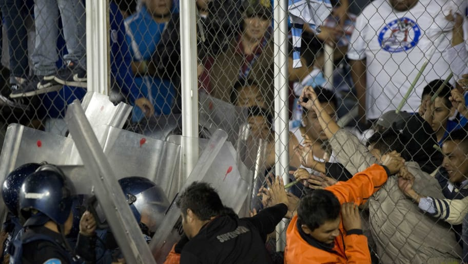 Angry fans of Cruz Azul team struggle with security personnel and riot policemen as they to push the fence to invade the field after their Apertura 2013 Mexican tournament football match against Toluca at the Cruz Azul stadium in Mexico City on November 30, 2013. The match ended 1-1 in a draw. AFP PHOTO/ Yuri CORTEZ        (Photo credit should read YURI CORTEZ/AFP/Getty Images)