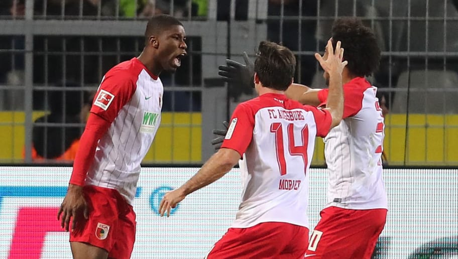 DORTMUND, GERMANY - FEBRUARY 26:  Kevin Danso of Augsburg celebrates scoring the equalizing goal with teamates during the Bundesliga match between Borussia Dortmund and FC Augsburg at Signal Iduna Park on February 26, 2018 in Dortmund, Germany.  (Photo by Christof Koepsel/Bongarts/Getty Images)