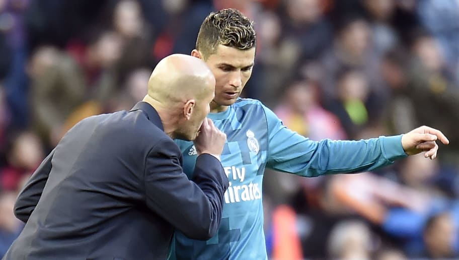 Real Madrid's French coach Zinedine Zidane talks to Real Madrid's Portuguese forward Cristiano Ronaldo (R) during the Spanish league football match between Valencia CF and Real Madrid CF at the Mestalla stadium in Valencia on January 27, 2018. / AFP PHOTO / JOSE JORDAN        (Photo credit should read JOSE JORDAN/AFP/Getty Images)