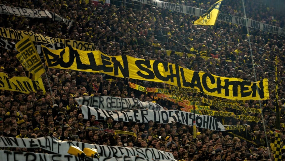 This picture taken on February 4, 2017 shows supporters of Dortmund displaying banners prior to the German First division Bundesliga football match between Borussia Dortmund and RB Leipzig, in Dortmund, western Germany.  / AFP PHOTO / SASCHA SCHUERMANN / RESTRICTIONS: DURING MATCH TIME: DFL RULES TO LIMIT THE ONLINE USAGE TO 15 PICTURES PER MATCH AND FORBID IMAGE SEQUENCES TO SIMULATE VIDEO. == RESTRICTED TO EDITORIAL USE == FOR FURTHER QUERIES PLEASE CONTACT DFL DIRECTLY AT + 49 69 650050         (Photo credit should read SASCHA SCHUERMANN/AFP/Getty Images)