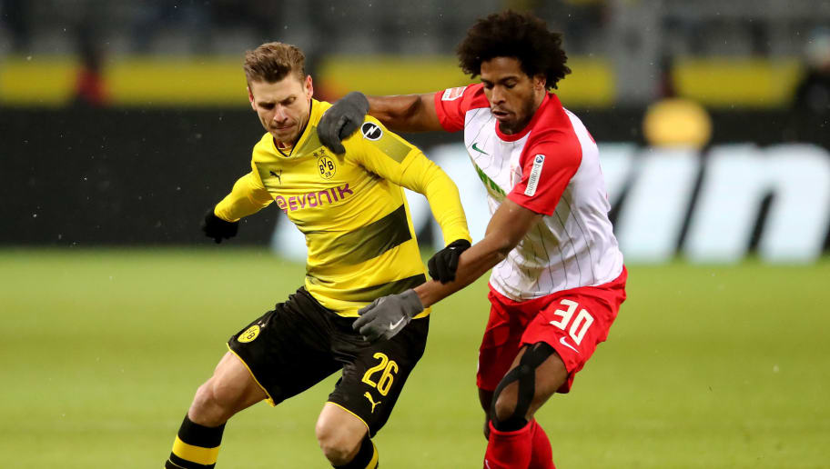 DORTMUND, GERMANY - FEBRUARY 26: Caiuby of Augsburg (R) challenges Lukasz Piszczek of Dortmund during the Bundesliga match between Borussia Dortmund and FC Augsburg at Signal Iduna Park on February 26, 2018 in Dortmund, Germany. (Photo by Christof Koepsel/Bongarts/Getty Images)