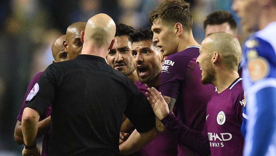 Referee Anthony Taylor (L) talks to Manchester City players after giving a red card to Manchester City's English midfielder Fabian Delph during the English FA Cup fifth round football match between Wigan Athletic and Manchester City at the DW Stadium in Wigan, northwest England, on February 19, 2018. / AFP PHOTO / Oli SCARFF / RESTRICTED TO EDITORIAL USE. No use with unauthorized audio, video, data, fixture lists, club/league logos or 'live' services. Online in-match use limited to 75 images, no video emulation. No use in betting, games or single club/league/player publications.  /         (Photo credit should read OLI SCARFF/AFP/Getty Images)