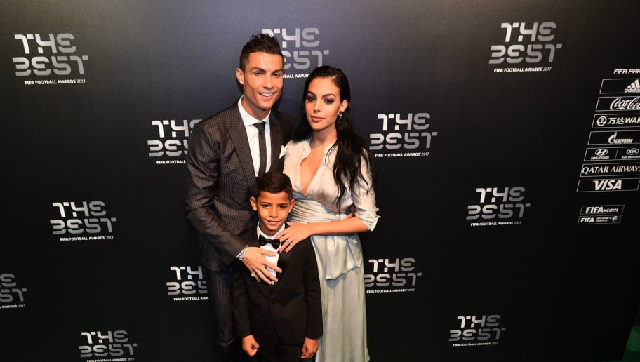 Real Madrid and Portugal forward Cristiano Ronaldo (L) poses for a photograph with partner Georgina Rodriguez (R) and his son Cristiano Ronaldo Jr as he arrives for The Best FIFA Football Awards ceremony, on October 23, 2017 in London. / AFP PHOTO / Glyn KIRK        (Photo credit should read GLYN KIRK/AFP/Getty Images)