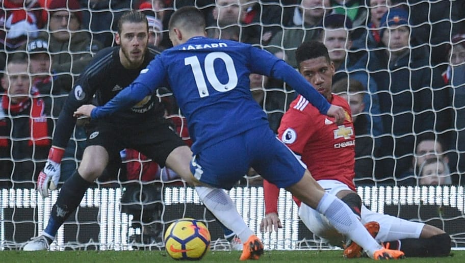 Chelsea's Belgian midfielder Eden Hazard (C) turns in the area but doesn't manage to get a shot off as Manchester United's Spanish goalkeeper David de Gea (L) and Manchester United's English defender Chris Smalling defend during the English Premier League football match between Manchester United and Chelsea at Old Trafford in Manchester, north west England, on February 25, 2018. / AFP PHOTO / Oli SCARFF / RESTRICTED TO EDITORIAL USE. No use with unauthorized audio, video, data, fixture lists, club/league logos or 'live' services. Online in-match use limited to 75 images, no video emulation. No use in betting, games or single club/league/player publications.  /         (Photo credit should read OLI SCARFF/AFP/Getty Images)