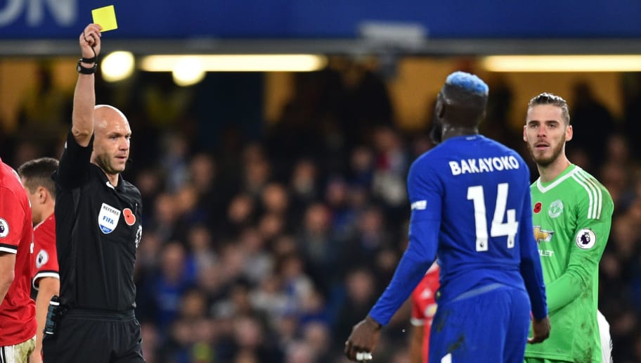 English referee Anthony Taylor (L) shows a yellow card to Chelsea's French midfielder Tiemoue Bakayoko during the English Premier League football match between Chelsea and Manchester United at Stamford Bridge in London on November 5, 2017. / AFP PHOTO / Glyn KIRK / RESTRICTED TO EDITORIAL USE. No use with unauthorized audio, video, data, fixture lists, club/league logos or 'live' services. Online in-match use limited to 75 images, no video emulation. No use in betting, games or single club/league/player publications.  /         (Photo credit should read GLYN KIRK/AFP/Getty Images)