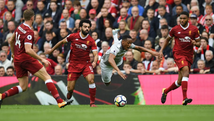 Manchester United's French striker Anthony Martial (2nd R) falls under a challenge from Liverpool's Egyptian midfielder Mohamed Salah (2nd L) during the English Premier League football match between Liverpool and Manchester United at Anfield in Liverpool, north west England on October 14, 2017. / AFP PHOTO / Paul ELLIS / RESTRICTED TO EDITORIAL USE. No use with unauthorized audio, video, data, fixture lists, club/league logos or 'live' services. Online in-match use limited to 75 images, no video emulation. No use in betting, games or single club/league/player publications.  /         (Photo credit should read PAUL ELLIS/AFP/Getty Images)
