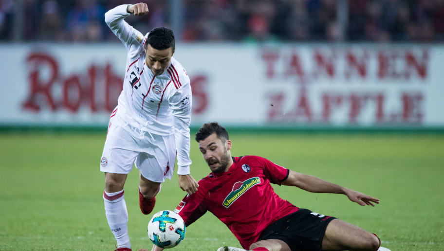 FREIBURG IM BREISGAU, GERMANY - MARCH 04: Thiago of Muenchen is challenged by Manuel Gulde of Freiburg during the Bundesliga match between Sport-Club Freiburg and FC Bayern Muenchen at Schwarzwald-Stadion on March 4, 2018 in Freiburg im Breisgau, Germany. (Photo by Simon Hofmann/Bongarts/Getty Images)