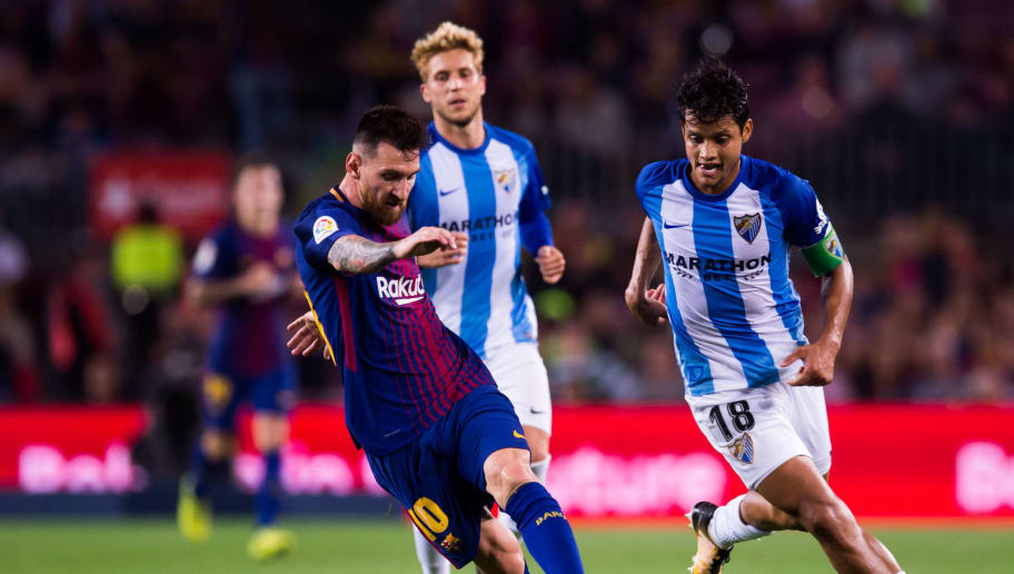 BARCELONA, SPAIN - OCTOBER 21:  Lionel Messi of FC Barcelona conducts the ball under pressure from Roberto Rosales of Malaga CF during the La Liga match between Barcelona and Malaga at Camp Nou on October 21, 2017 in Barcelona, Spain.  (Photo by Alex Caparros/Getty Images)