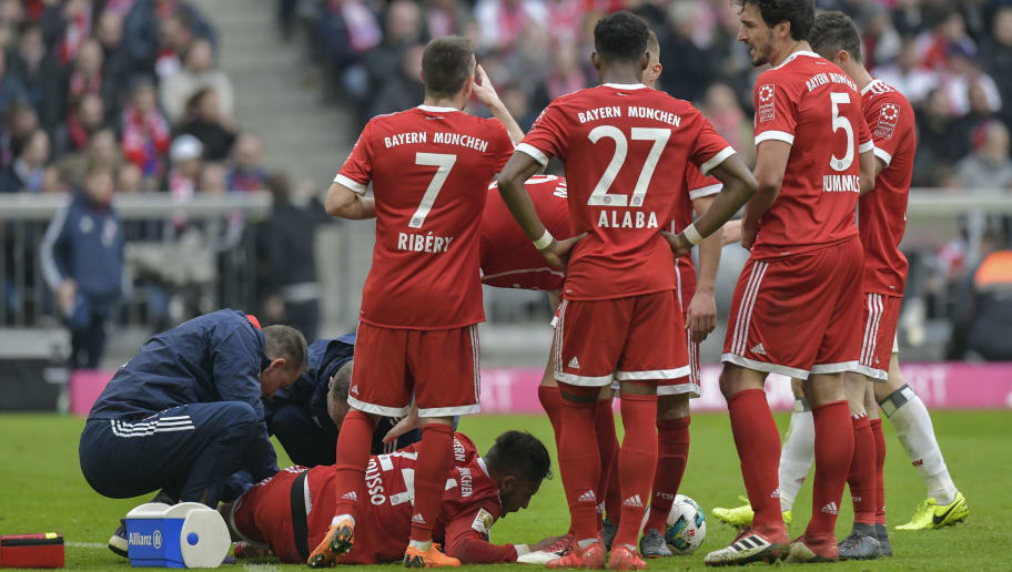 Bayern Munich's French midfielder Corentin Tolisso (bottom) lies on the pitch after being injured during the German first division Bundesliga football match Bayern Munich vs Hamburger SV in Munich on March 10, 2018. / AFP PHOTO / Guenter SCHIFFMANN / RESTRICTIONS: DURING MATCH TIME: DFL RULES TO LIMIT THE ONLINE USAGE TO 15 PICTURES PER MATCH AND FORBID IMAGE SEQUENCES TO SIMULATE VIDEO. == RESTRICTED TO EDITORIAL USE == FOR FURTHER QUERIES PLEASE CONTACT DFL DIRECTLY AT + 49 69 650050         (Photo credit should read GUENTER SCHIFFMANN/AFP/Getty Images)