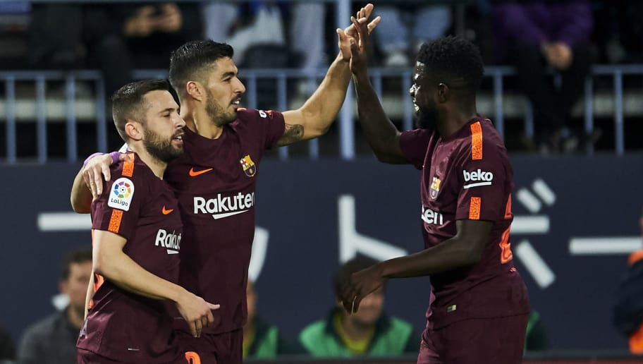 MALAGA, SPAIN - MARCH 10:  Luis Suarez of FC Barcelona celebrates with his teammate Jordi Alba and Samuel Umtiti of FC Barcelona after scoring the opening goal during the La Liga match between Malaga and Barcelona at Estadio La Rosaleda on March 10, 2018 in Malaga, Spain.  (Photo by Aitor Alcalde/Getty Images)