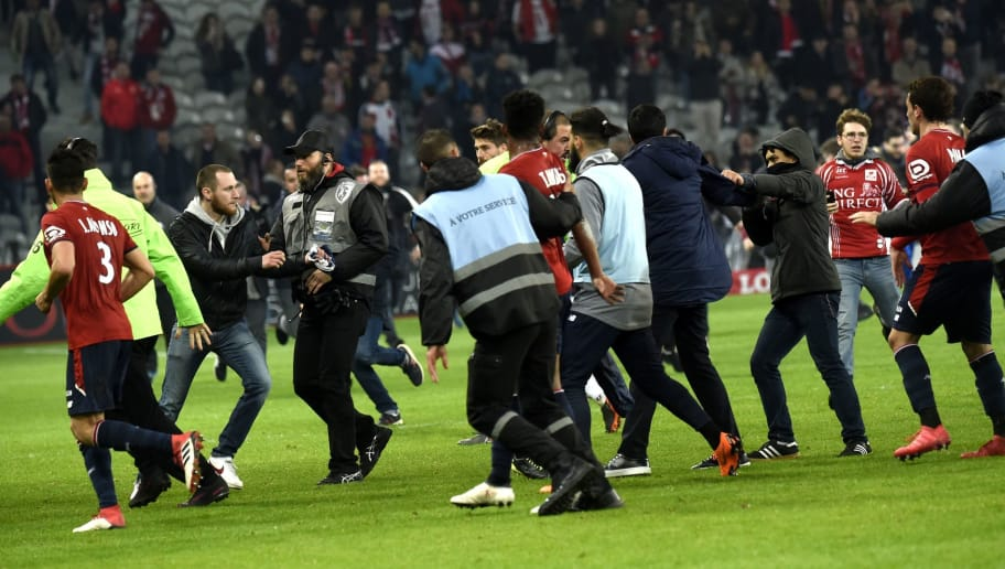 Lille' supporters invade the pitch at the end of  the French L1 football match between Lille and Montpellier on March 10, 2018 at the Pierre Mauroy stadium in Lille, northern France.  / AFP PHOTO / FRANCOIS LO PRESTI        (Photo credit should read FRANCOIS LO PRESTI/AFP/Getty Images)