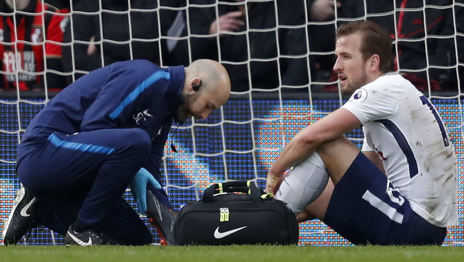 Tottenham Hotspur's English striker Harry Kane (R) receives medical attention after picking up an injury during the English Premier League football match between Bournemouth and Tottenham Hotspur at the Vitality Stadium in Bournemouth, southern England on March 11, 2018. / AFP PHOTO / Adrian DENNIS / RESTRICTED TO EDITORIAL USE. No use with unauthorized audio, video, data, fixture lists, club/league logos or 'live' services. Online in-match use limited to 75 images, no video emulation. No use in betting, games or single club/league/player publications.  /         (Photo credit should read ADRIAN DENNIS/AFP/Getty Images)