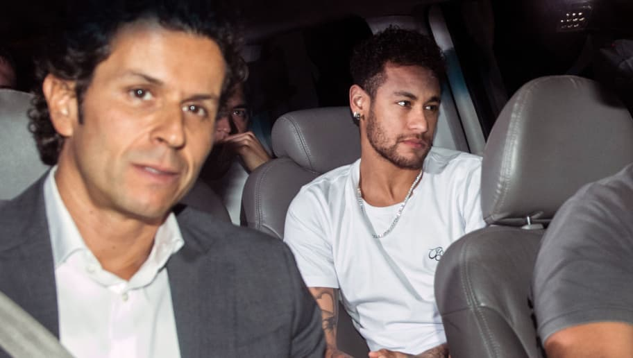 TOPSHOT - Brazilian superstar Neymar (R), is pictured next to his doctor Rodrigo Lasmar (L), upon his arrival in Belo Horizonte, Minas Gerais state, Brazil on March 2, 2018 ahead of an operation on his fractured foot.  Brazilian superstar Neymar arrived in Belo Horizonte later Friday for surgery to mend a broken bone in his right foot, while an anxious footballing nation wondered if its World Cup build-up will also need urgent care. / AFP PHOTO / NELSON ALMEIDA        (Photo credit should read NELSON ALMEIDA/AFP/Getty Images)