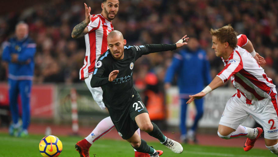 STOKE ON TRENT, ENGLAND - MARCH 12:  David Silva of Manchester City evades Geoff Cameron and Moritz Bauer of Stoke City during the Premier League match between Stoke City and Manchester City at Bet365 Stadium on March 12, 2018 in Stoke on Trent, England.  (Photo by Gareth Copley/Getty Images)