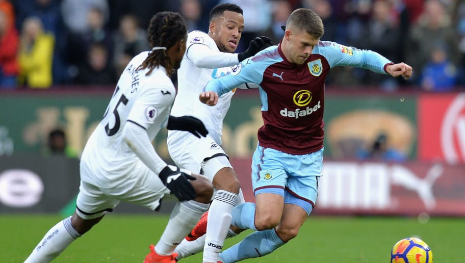 BURNLEY, ENGLAND - NOVEMBER 18:  Johann Gudmundsson (R) of Burnley competes for the ball against Jordan Ayew (C) and Renato Sanches (L) of Swansea City  during the Premier League match between Burnley and Swansea City at Turf Moor on November 18, 2017 in Burnley, England.  (Photo by Mark Runnacles/Getty Images)