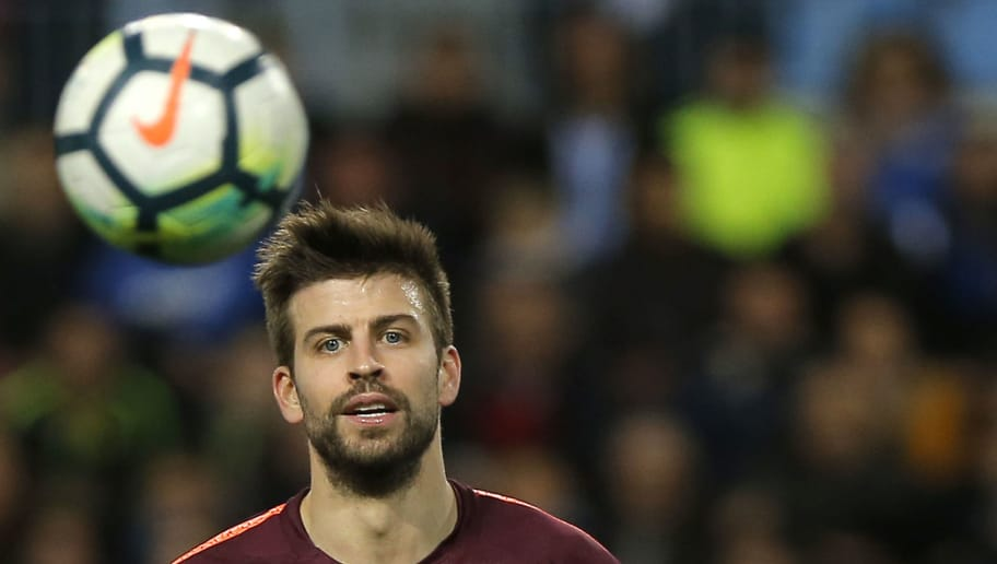 Barcelona's Spanish defender Gerard Pique looks at the ball during the Spanish league football match between Malaga CF and FC Barcelona at the La Rosaleda stadium in Malaga on March 10, 2018. / AFP PHOTO / STRINGER        (Photo credit should read STRINGER/AFP/Getty Images)