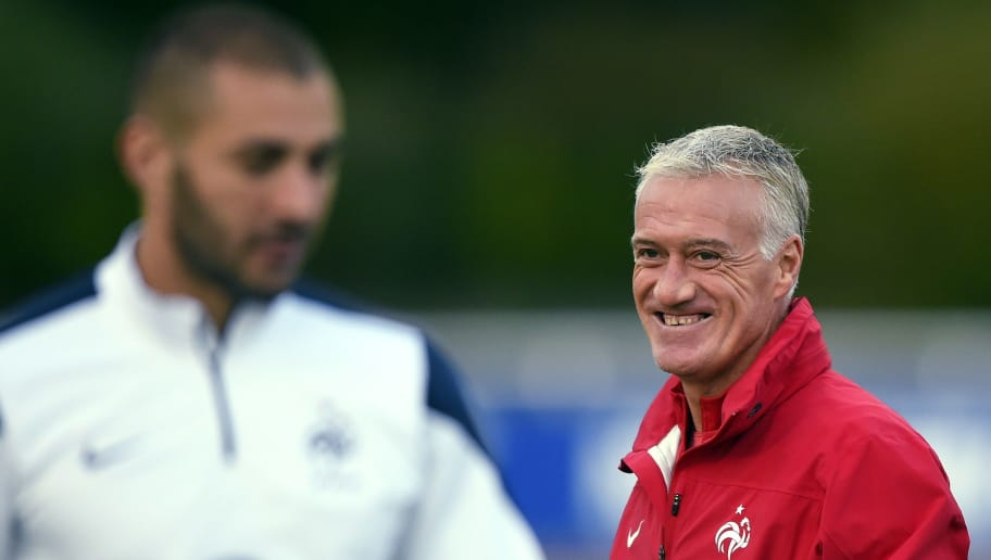French head coach Didier Deschamps (R) stands behind French forward Karim Benzema during a training session in Clairefontaine-en-Yvelines on October 7, 2014 ahead of a friendly football match opposing France to Portugal to be held on October 11 at the Stade de France in Saint-Denis, outside Paris. AFP PHOTO / FRANCK FIFE        (Photo credit should read FRANCK FIFE/AFP/Getty Images)