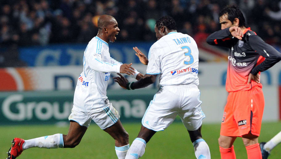 Olympique Marseille's midfielder from Burkina Faso Charles Kabore (L) is congratuled by Olympique Marseille's Nigerian defender Taye Taiwo (C) next to Lyon's forward Cesar Delgado Godoy (R) after scoring a goal during their French L1 match Marseille versus Lyon, on March 21, 2010 at the Velodrome stadium in Marseille.      AFP PHOTO GERARD JULIEN (Photo credit should read GERARD JULIEN/AFP/Getty Images)