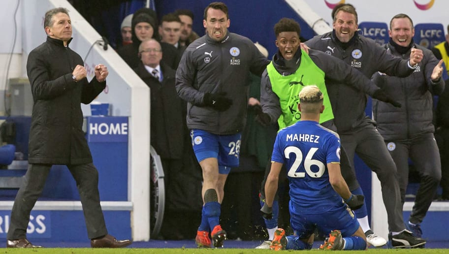 Leicester City's French manager Claude Puel (L) reacts as Leicester City's Algerian midfielder Riyad Mahrez (C) celebrates scoring his late goal with teammates and staff during the English Premier League football match between Leicester City and Bournemouth at King Power Stadium in Leicester, central England on March 3, 2018. The game finished 1-1. / AFP PHOTO / Roland HARRISON / RESTRICTED TO EDITORIAL USE. No use with unauthorized audio, video, data, fixture lists, club/league logos or 'live' services. Online in-match use limited to 75 images, no video emulation. No use in betting, games or single club/league/player publications.  /         (Photo credit should read ROLAND HARRISON/AFP/Getty Images)