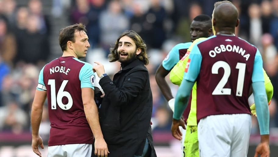 A pitch invader (2L) confronts West Ham United's English midfielder Mark Noble (L) during the English Premier League football match between West Ham United and Burnley at The London Stadium, in east London on March 10, 2018. / AFP PHOTO / Ben STANSALL / RESTRICTED TO EDITORIAL USE. No use with unauthorized audio, video, data, fixture lists, club/league logos or 'live' services. Online in-match use limited to 75 images, no video emulation. No use in betting, games or single club/league/player publications.  /         (Photo credit should read BEN STANSALL/AFP/Getty Images)