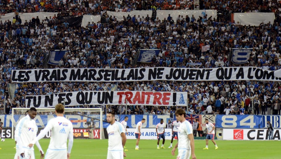 In this picture taken on September 20, 2015 Marseille supporters display banners against rivals Olympique Lyonaise during the French L1 football match Marseille (OM) vs Lyon (OL)  at the Velodrome Stadium in Marseille, southern France.  Play was resumed after an interuption of 20 minutes caused by trouble from rival spectators.  AFP PHOTO / FRANCK PENNANT        (Photo credit should read FRANCK PENNANT/AFP/Getty Images)