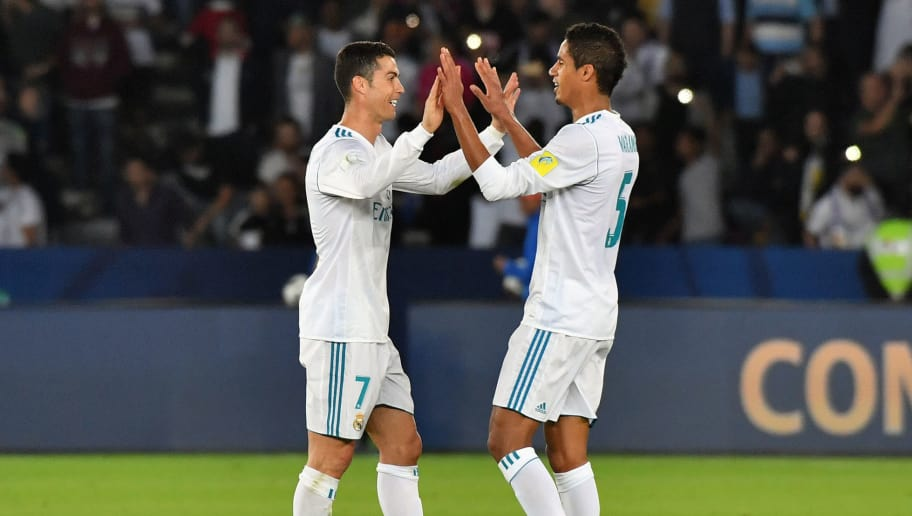 Real Madrid's Portuguese forward Ronaldo (L) celebrates with teammate French defender Raphael Varane after winning FIFA Club World Cup 2017 final football match at Zayed Sports City Stadium in the Emirati capital Abu Dhabi on December 16, 2017. Real Madrid defeated Gremio 1-0 to lift the FIFA Club World Cup for the third time in their history. / AFP PHOTO / Giuseppe CACACE        (Photo credit should read GIUSEPPE CACACE/AFP/Getty Images)