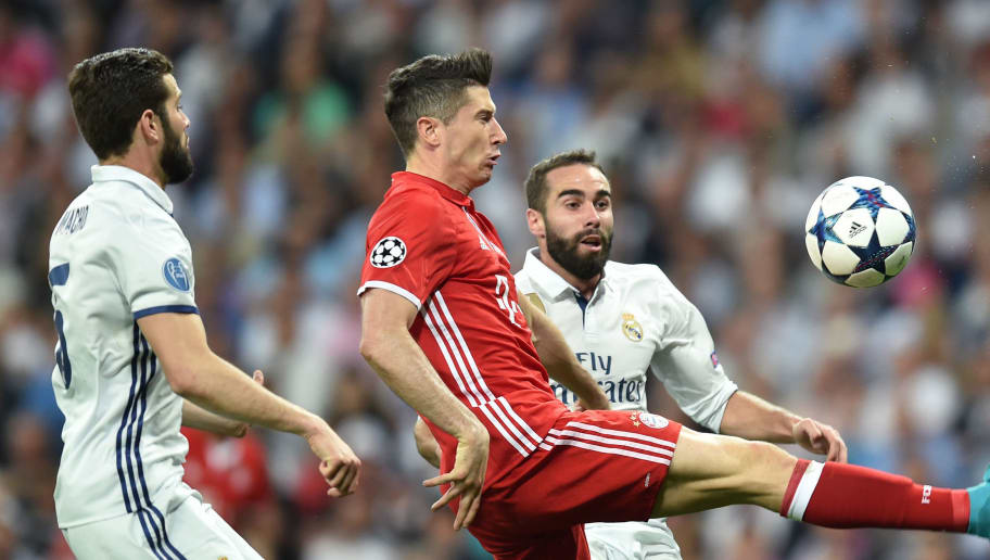 (L-R) Real Madrid's French defender Raphael Varane, Bayern Munich's Polish striker Robert Lewandowski and Real Madrid's defender Daniel Carvajas vie for the ball during the UEFA Champions League quarter-final second leg football match Real Madrid vs FC Bayern Munich at the Santiago Bernabeu stadium in Madrid in Madrid on April 18, 2017. / AFP PHOTO / Christof STACHE        (Photo credit should read CHRISTOF STACHE/AFP/Getty Images)