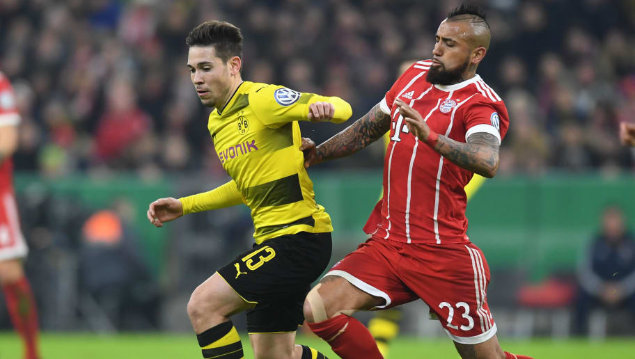 Dortmund's Portuguese defender Raphael Guerreiro (L) vies with Bayern Munich's Chilian midfielder Arturo Vidal (R) during the German football Cup DFB Pokal round of sixteen match Bayern Munich vs Dortmund on December 20, 2017 in Munich.  / AFP PHOTO / Christof STACHE / RESTRICTIONS: ACCORDING TO DFB RULES IMAGE SEQUENCES TO SIMULATE VIDEO IS NOT ALLOWED DURING MATCH TIME. MOBILE (MMS) USE IS NOT ALLOWED DURING AND FOR FURTHER TWO HOURS AFTER THE MATCH. == RESTRICTED TO EDITORIAL USE == FOR MORE INFORMATION CONTACT DFB DIRECTLY AT +49 69 67880   /         (Photo credit should read CHRISTOF STACHE/AFP/Getty Images)