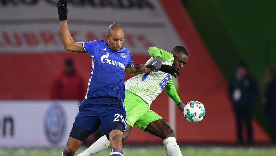 WOLFSBURG, GERMANY - MARCH 17: Naldo of Schalke (l) fights for the ball with Landry Dimata of Wolfsburg during the Bundesliga match between VfL Wolfsburg and FC Schalke 04 at Volkswagen Arena on March 17, 2018 in Wolfsburg, Germany. (Photo by Stuart Franklin/Bongarts/Getty Images)