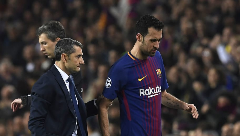 Barcelona's Spanish midfielder Sergio Busquets (R) walks with Barcelona's Spanish coach Ernesto Valverde as he is substituted during the UEFA Champions League round of sixteen second leg football match between FC Barcelona and Chelsea FC at the Camp Nou stadium in Barcelona on March 14, 2018. / AFP PHOTO / LLUIS GENE        (Photo credit should read LLUIS GENE/AFP/Getty Images)