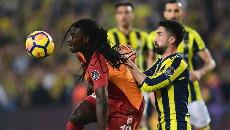 Galatasaray's Bafetimbi Gomis (L) kicks the ball next to Fenerbahce's defender Hasan Ali Kaldirim (R) during the   Turkish Super Lig football match between Fenerbahce and Galatasaray on March 17, 2018, at the Fenerbahce Ulker Stadium in Istanbul. / AFP PHOTO / OZAN KOSE        (Photo credit should read OZAN KOSE/AFP/Getty Images)