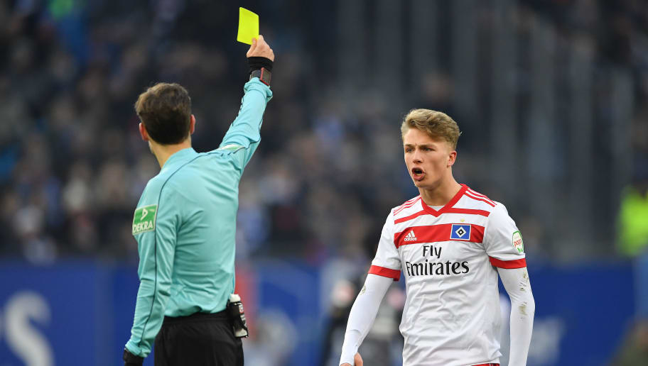 HAMBURG, GERMANY - MARCH 03: Jann-Fiete Arp of Hamburg is shown a yellow card by referee Marco Fritz during the Bundesliga match between Hamburger SV and 1. FSV Mainz 05 at Volksparkstadion on March 3, 2018 in Hamburg, Germany. (Photo by Stuart Franklin/Bongarts/Getty Images)