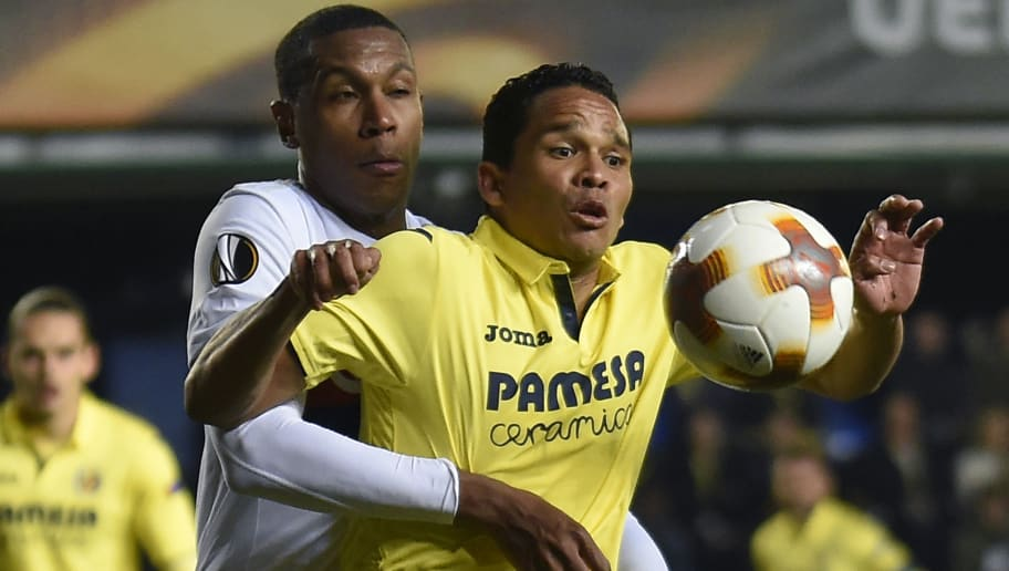 Lyon's Brazilian defender Marcelo (L) vies with Villarreal's Colombian forward Carlos Bacca during the Europa League Round of 32 second leg football match between Villarreal CF and Olympique Lyonnais at La Ceramica stadium in Vila-real on February 22, 2018. / AFP PHOTO / JOSE JORDAN        (Photo credit should read JOSE JORDAN/AFP/Getty Images)