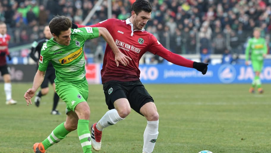 HANOVER, GERMANY - FEBRUARY 24: Jonas Hofmann (L) of Moenchengladbach tackles Josip Elez of Hannover during the Bundesliga match between Hannover 96 and Borussia Moenchengladbach at HDI-Arena on February 24, 2018 in Hanover, Germany. (Photo by Thomas Starke/Bongarts/Getty Images)