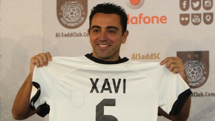 Barcelona legend Xavi Hernandez gestures in his new Al-Sadd club shirt after signing a two-year contract with the Qatari football team in Doha on June 11, 2015. AFP PHOTO / STR        (Photo credit should read STR/AFP/Getty Images)