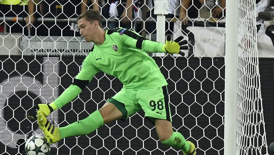 Dinamo Zagreb's Croatian goalkeeper Adrian Semper fails to stop the ball during the Champions League Group H football match between Olympique Lyonnais and Dinamo Zagreb at the Parc Olympique Lyonnais in Decines-Charpieu on September 14, 2016.  / AFP / PHILIPPE DESMAZES        (Photo credit should read PHILIPPE DESMAZES/AFP/Getty Images)