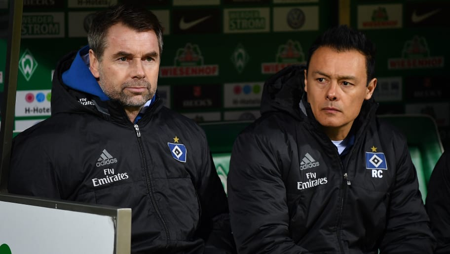BREMEN, GERMANY - FEBRUARY 24: Bernd Hollerbach, coach of Hamburg, (l) and Rodolfo Cardoso, assistant coach of Hamburg, sit on the bench during the Bundesliga match between SV Werder Bremen and Hamburger SV at Weserstadion on February 24, 2018 in Bremen, Germany. (Photo by Stuart Franklin/Bongarts/Getty Images)