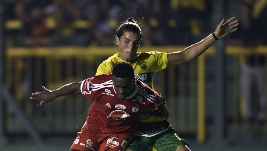Colombia's America de Cali forward Cristian Arboleda (foreground) is fouled by Argentina's Defensa y Justicia Swiss defender Dylan Gissi during their Copa Sudamericana first stage first leg football match at the Norberto Tomaghello stadium in Florencio Varela, Buenos Aires, on February 15, 2018. / AFP PHOTO / Juan MABROMATA        (Photo credit should read JUAN MABROMATA/AFP/Getty Images)