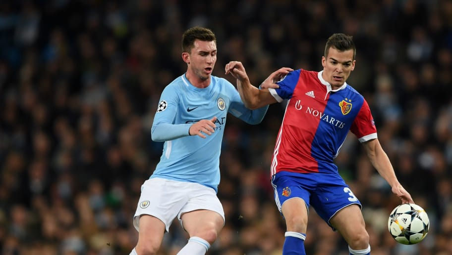 MANCHESTER, ENGLAND - MARCH 07: Kevin Bua of FC Basel holds off pressure from Aymeric Laporte of Manchester City during the UEFA Champions League Round of 16 Second Leg match between Manchester City and FC Basel at Etihad Stadium on March 7, 2018 in Manchester, United Kingdom.  (Photo by Shaun Botterill/Getty Images)