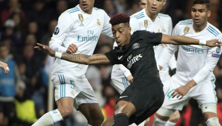 Paris Saint-Germain's French defender Presnel Kimpembe (front) kicks the ball beside Real Madrid's French defender Raphael Varane, Real Madrid's Portuguese forward Cristiano Ronaldo and Real Madrid's Brazilian midfielder Casemiro (back L-R) during the UEFA Champions League round of sixteen first leg football match Real Madrid CF against Paris Saint-Germain (PSG) at the Santiago Bernabeu stadium in Madrid on February 14, 2018.   / AFP PHOTO / CURTO DE LA TORRE        (Photo credit should read CURTO DE LA TORRE/AFP/Getty Images)