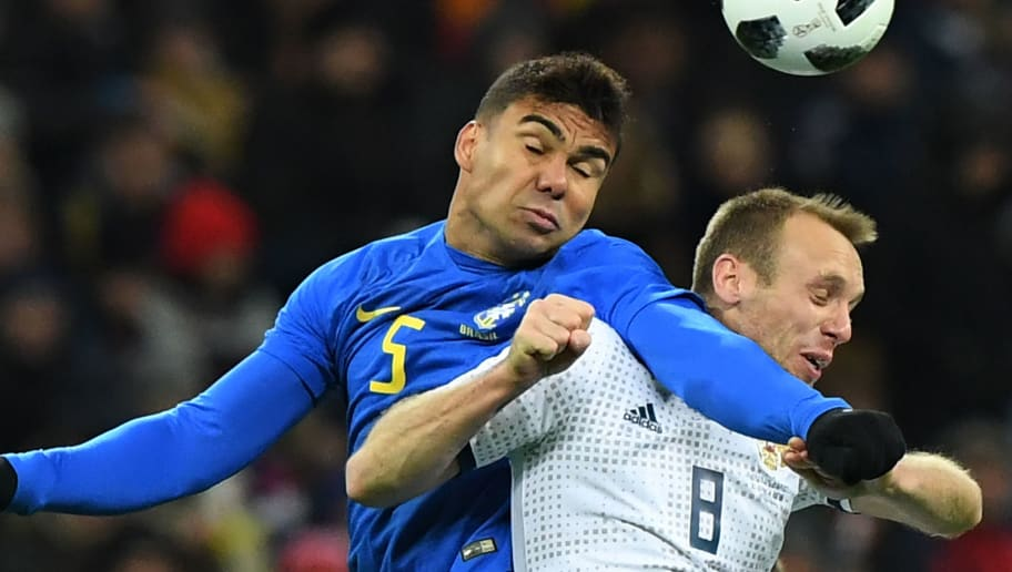 Brazil's midfielder Casemiro (L) and Russia's midfielder Denis Glushakov vie for the ball during an international friendly football match between Russia and Brazil at the Luzhniki stadium in Moscow on March 23, 2018. / AFP PHOTO / Kirill KUDRYAVTSEV        (Photo credit should read KIRILL KUDRYAVTSEV/AFP/Getty Images)